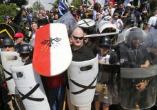 FILE - In this Aug. 12, 2017 file photo, white nationalist demonstrators use shields as they guard the entrance to Lee Park in Charlottesville, Va. The American Civil Liberties Union is reeling from criticism for its role in defending the right of white supremacists' right to march in Charlottesvile. After that rally left a counter protester dead, some critics said the ACLU had blood on its hands. (AP Photo/Steve Helber, File)