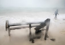 A person walks past a damaged staircase on Cofrecito Beach after the crossing of Hurricane Maria over Bavaro, Dominican Republic, Thursday, Sept. 21, 2017. Rain from the storm will continue in the Dominican Republic for the next two days according to meteorologists.(AP Photo/Tatiana Fernandez)