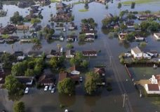 In this arial photo, homes sit in floodwaters caused Tropical Storm Harvey in Port Arthur, Texas, Friday, Sept. 1, 2017.  Port Arthur's major roads were swamped by rising waters brought by Harvey(AP Photo/LM Otero)