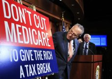 Senate Minority Leader Chuck Schumer of New York, followed by Sen. Bernie Sanders, I-Vt., look at a poster at the start of a news conference on Capitol Hill in Washington, Wednesday, October 4, 2017, urging Republicans to abandon cuts to Medicare and Medicaid. (AP Photo/Manuel Balce Ceneta)
