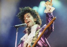 FILE - In this Feb. 18, 1985 file photo, Prince performs at the Forum in Inglewood, Calif. A pair of floral-patterned satin shoes worn by Prince has stepped into the collection of Britain's Victoria & Albert Museum. (AP Photo/Liu Heung Shing, File)