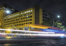 Traffic along Pennsylvania Avenue in Washington streaks past the Federal Bureau of Investigation headquarters building Wednesday night, Nov. 1, 2017. Scores of U.S. diplomatic, military and government figures were not told about attempts to hack into their emails even though the FBI knew they were in the Kremlin's crosshairs, The Associated Press has learned. (AP Photo/J. David Ake)