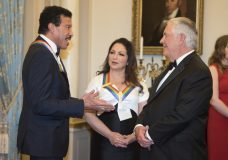Secretary of State Rex Tillerson, right, talks with 2017 Kennedy Center Honorees Lionel Richie and Gloria Estefan, center, following the State Department dinner for the Kennedy Center Honors, Saturday, Dec. 2, 2017, in Washington. (AP Photo/Kevin Wolf)