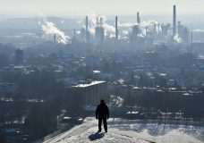 FILE - In this Jan. 19, 2016 file photo, a man watches a BP refinery in Gelsenkirchen, Germany. New York City officials say they will begin the process of dumping about $5 billion in pension fund investments in fossil fuel companies, including BP, because of environmental concerns. (AP Photo/Martin Meissner, File)