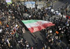 In this photo provided by Tasnim News Agency, a demonstrator waves a huge Iranian flag during a pro-government rally in the northeastern city of Mashhad, Iran, Thursday, Jan. 4, 2018. The strength of protests shaking Iran was unclear on Thursday after a week of unrest that killed at least 21 people, with fewer reports of demonstrations as government supporters again took to the streets in several cities and towns. (Nima Najafzadeh/Tasnim News Agency via AP)
