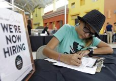 FILE - In this Tuesday, Oct. 3, 2017, file photo, Job seeker Alejandra Bastidas fills out an application at a job fair, at Dolphin Mall in Sweetwater, Fla. Employers posted fewer open jobs in November, the second straight month of decline after openings reached a record high in September. (AP Photo/Alan Diaz, File)