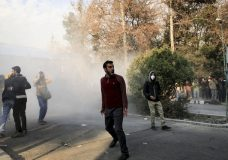 In this photo taken by an individual not employed by the Associated Press and obtained by the AP outside Iran, university students attend a protest inside Tehran University while a smoke grenade is thrown by anti-riot Iranian police, in Tehran, Iran, Saturday, Dec. 30, 2017. A wave of spontaneous protests over Iran's weak economy swept into Tehran on Saturday, with college students and others chanting against the government just hours after hard-liners held their own rally in support of the Islamic Republic's clerical establishment. (AP Photo)
