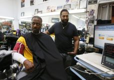 CORRECTS CITY TO INGLEWOOD FROM LOS ANGELES - In this Sunday, March 11, 2018, photo, Barber Eric Muhammad, owner of A New You Barbershop measures the blood pressure of customer Marc M. Sims in Inglewood, Calif. Black male customers at dozens of Los Angeles area barbershops reduced one of their biggest health risks through a novel project that paired barbers and pharmacists to test and treat customers. (AP Photo/Damian Dovarganes)