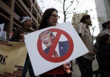 Jill Green holds a sign during a rally against a scheduled upcoming visit by President Donald Trump, Monday, March 12, 2018, in San Diego. Trump is scheduled to visit San Diego, Tuesday, setting foot in California for his first time as president. (AP Photo/Gregory Bull)