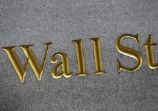 FILE - This July 6, 2015, file photo shows a sign for Wall Street carved into the side of a building in New York. The U.S. stock market opens at 9:30 a.m. EDT on Thursday, March 29, 2018. (AP Photo/Mark Lennihan, File)