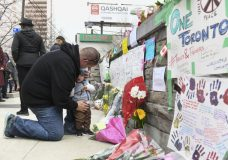 Sean O'Keefe and his son Fionn, 16 months, bring flowers to a memorial on Yonge Street Tuesday, April 24, 2018, in Toronto, the day after a driver drove a van down sidewalks, striking and killing numerous pedestrians in his path. (Galit Rodan/The Canadian Press via AP)