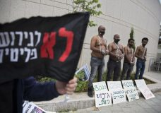 """African migrants wear chains to represent slavery during a demonstration in Tel Aviv, Israel, Tuesday, April 3, 2018. Israel announced a deal with the U.N. on Monday to resettle African migrants in Western nations, but hours later put the agreement on hold. Hebrew sign reads: """"No to the deportation of migrants"""". (AP Photo/Sebastian Scheiner)"""