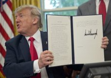 President Donald Trump holds up the executive order he signed to end family separations at the border, during an event in the Oval Office of the White House in Washington, Wednesday, June 20, 2018. (AP Photo/Pablo Martinez Monsivais)