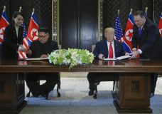 FILE - In this Tuesday, June 12, 2018, file photo, North Korea leader Kim Jong Un and U.S. President Donald Trump prepare to sign a document at the Capella resort on Sentosa Island in Singapore. At the ceremony, a gloved North Korean official inspected Kim's chair and the black felt-tipped pen bearing Trump's signature in gold that was positioned for Kim's use. At the last minute, Kim's sister, Kim Yo-jong, far left, provided a pen of her own for his use. (AP Photo/Evan Vucci, File)