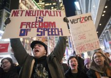 FILE - In this Thursday, Dec. 7, 2017 file photo, Demonstrators rally in support of net neutrality outside a Verizon store in New York. Consumers aren't likely to see immediate changes following Monday, June 11, 2018 formal repeal of Obama-era internet rules that had ensured equal treatment for all. Rather, any changes are likely to happen slowly, and companies will try to make sure that consumers are on board with the moves, experts say. (AP Photo/Mary Altaffer, File)