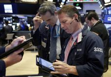 Traders Gregory Rowe, center, and Robert Charmak work on the floor of the New York Stock Exchange, Monday, June 11, 2018. Stocks are opening higher on some corporate deal news. (AP Photo/Richard Drew)