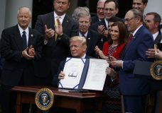 """President Donald Trump shows off the """"VA Mission Act"""" during a signing ceremony in the Rose Garden of the White House, Wednesday, June 6, 2018, in Washington. (AP Photo/Evan Vucci)"""