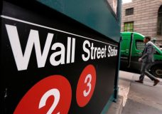 FILE- In this April 5, 2018, file photo, a sign for a Wall Street subway station is shown in New York. The U.S. stock market opens at 9:30 a.m. EDT on Monday, June 25. (AP Photo/Richard Drew, File)