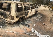 A burned vehicle is seen in the mountain community of Keswick, Calif., Sunday, July 29, 2018. On Sunday, the San Bernardino County Fire department pulled in to tamp down smoking rubble. Piles of wreckage were still smoking amid downed electricity lines. (AP Photo/Martha Mendoza)