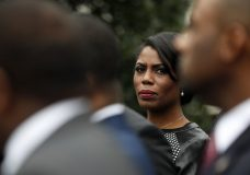 """FILE - In this Feb. 28, 2017 file photo, White House Director of communications for the Office of Public Liaison Omarosa Manigault Newman stands with the of leaders of Historically Black Colleges and Universities (HBCU) outside the West Wing of the White House in Washington. The White House says former aide Omarosa Manigault Newman has """"shown a complete lack of integrity"""" with her criticism of President Donald Trump in her new book, """"Unhinged."""" Press secretary Sarah Huckabee Sanders said Tuesday, Aug. 14, 2018, that Trump's tweets referring to Manigault Newman as """"crazed"""" and a """"dog"""" reflect his """"frustration"""" with her comments. (AP Photo/Pablo Martinez Monsivais)"""