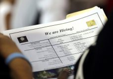 FILE In this June 21, 2018 file photo, a job applicant looks at job listings for the Riverside Hotel at a job fair hosted by Job News South Florida, in Sunrise, Fla. Economists forecast that employers added 191,000 jobs in July, down from 213,000 in June but easily enough to lower the unemployment rate over time. The jobless rate is projected to decline to 3.9 percent, near an 18-year low, from 4 percent. The Labor Department's monthly jobs report will be released at 8:30 a.m. Eastern Friday, Aug. 3. (AP Photo/Lynne Sladky)