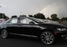 FILE- In this July 8, 2018, file photo a rainbow illuminates the sky as 2018 MKZ sedans MKX as they sit outside a Lincoln dealership in Englewood, Colo. On Wednesday, Aug 15, the Commerce Department releases U.S. retail sales data for July. (AP Photo/David Zalubowski, File)