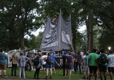 Banners are used to cover the statue known as Silent Sam as people gather during a rally to remove the confederate statue from campus at the University of North Carolina in Chapel Hill, N.C., Monday, Aug. 20, 2018. (AP Photo/Gerry Broome)
