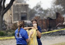 A resident, in yellow, wishing not to be identified, is comforted after seeing her fire-ravaged home for the first time Thursday, Aug. 2, 2018, in Redding, Calif. (AP Photo/Marcio Jose Sanchez)