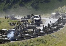 "FILE In this file photo taken on Saturday, Aug. 9, 2008, A column of Russian armoured vehicles seen on their way to the South Ossetian capital Tskhinvali somewhere in the Georgian breakaway region, South Ossetia, Georgia. The Russian military quickly routed the Georgian army during the August 2008 war. Russia's Prime Minister Dmitry Medvedev in an interview broadcast by Russian state television Tuesday Aug. 7, 2018, on the 10th anniversary of the Russia-Georgia war, issued a stern warning that incorporating Georgia into NATO could trigger a new ""horrible"" conflict.(AP Photo/Musa Sadulayev, File)"