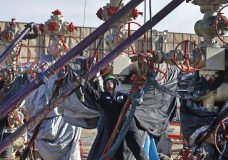 FILE - In this March 25, 2014 file photo, a worker adjusts pipes during a hydraulic fracturing operation at a well pad near Mead, Colorado. The Trump administration is moving to roll back Obama-era rules intended to reduce leaks of climate-changing methane from oil and gas facilities. The Environmental Protection Agency formally released a proposed substitute rule Tuesday. The EPA acknowledges the rollback would lead to more methane leaking into the atmosphere. The agency says relaxing oversight will save $75 million in regulatory costs annually. (AP Photo/Brennan Linsley, file)
