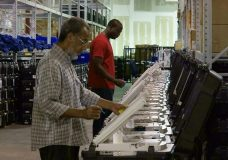 FILE - In this Sept. 22, 2016, file photo, employees of the Fulton County Election Preparation Center in Atlanta test electronic voting machines. Voting integrity advocates had argued Georgia's electronic voting machines are unreliable and vulnerable to hacking, but a federal judge says forcing the state to change its system to paper ballots before the midterm elections is too risky. (AP Photo/Alex Sanz, File)