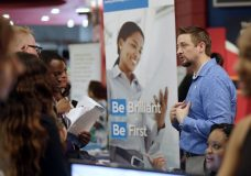 FILE- In this June 21, 2018, file photo, Chad Beutler, of First Data, right, talks with applicants at a job fair hosted by Job News South Florida, in Sunrise, Fla. On Wednesday, Oct. 3, the payroll processor ADP reports how many jobs private employers added in September. (AP Photo/Lynne Sladky, File)