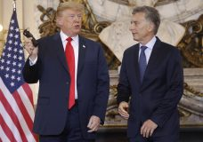 President Donald Trump, left, holds up his audio translator headphones as he speaks to Argentina's President Mauricio Macri, right, during their meeting at Casa Rosada, Friday, Nov. 30, 2018 in Buenos Aires, Argentina. (AP Photo/Pablo Martinez Monsivais)