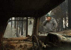 Troy Miller wipes his eyes as he walks beside a burned out car on his property in Concow, Calif. (AP Photo/John Locher)