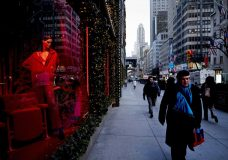 FILE - In this Wednesday, Dec. 5, 2018 file photo, people walk past a holiday window at Saks Fifth Avenue, in New York. U.S. consumer confidence tumbled this month as Americans began to worry that economic growth will moderate next year. The Conference Board, a business research group, says its consumer confidence index fell to 128.1 in December, down from 136.4 in November and lowest since July. (AP Photo/Mark Lennihan, File)
