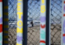 Two people embrace on the U.S. side of the border, seen through the border wall Monday, Jan. 7, 2019, seen from along the beach in Tijuana, Mexico. U.S. Vice President Mike Pence said Monday the White House is looking into the legality of declaring a national emergency to circumvent Congress and begin construction on President Donald Trump's long-promised Southern border wall. (AP Photo/Gregory Bull)