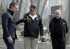 FILE - In this Nov. 17, 2018 file photo, President Donald Trump talks with Gov.-elect Gavin Newsom, left, as California Gov. Jerry Brown listens during a visit to a neighborhood impacted by the Camp wildfire in Paradise, Calif. President Donald Trump is threatening to withhold Federal Emergency Management Agency money to help California cope with wildfires if the state doesn't improve its forest management practices. Trump tweeted Wednesday, Jan. 9, 2019, that California gets billions of dollars for fires that could have been prevented with better management. (AP Photo/Evan Vucci, File)