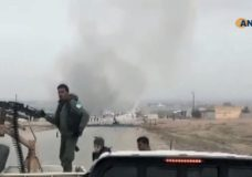 This frame grab from video provided by Hawar News, ANHA, the news agency for the semi-autonomous Kurdish areas in Syria, shows Kurdish fighters standing guard at the site of a suicide attack near the town of Shaddadeh, in Syria's northeastern province of Hassakeh, Syria, Monday, Jan. 21, 2019. The state news agency SANA and the Kurdish Hawar news agency, said that the blast was a suicide bombing that targeted a Syrian Kurdish checkpoint. (ANHA via AP)