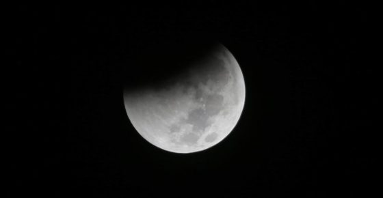 FILE - In this Saturday Aug. 28, 2018 file photo, Earth starts to cast its shadow on the moon during a complete lunar eclipse seen from Jakarta, Indonesia. Starting Sunday evening, Jan. 20, 2019, all of North and South America will be able to see the only total lunar eclipse of 2019 from start to finish this weekend. (AP Photo/Tatan Syuflana)