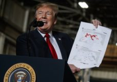 President Donald Trump holds up a chart documenting ISIS land loss in Iraq and Syria as delivers remarks at the Lima Army Tank Plant, Wednesday, March 20, 2019, in Lima, Ohio. In a campaign that spanned five years and two U.S. presidencies, the American military engineered the destruction of the Islamic State group's self-proclaimed empire in Iraq and Syria. That's a military success, but not one that's certain to last. (AP Photo/Evan Vucci)
