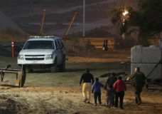 FILE - In this Dec. 3, 2018, file photo, migrants are escorted by a U.S. Border Patrol agent as they are detained after climbing over the border wall from Playas de Tijuana, Mexico, to San Ysidro, Calif. The Trump administration's effort to make asylum seekers wait in Mexico explicitly targets Spanish-speakers and people from Latin America, according to internal guidelines of a highly touted strategy to address the burgeoning number of Central Americans arriving at U.S. borders. (AP Photo/Rebecca Blackwell, File)