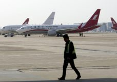 A ground crew walks near a Boeing 737 Max 8 plane operated by Shanghai Airlines parked on the tarmac at Hongqiao airport in Shanghai, China, Tuesday, March 12, 2019. U.S. aviation experts on Tuesday joined the investigation into the crash of an Ethiopian Airlines jetliner that killed 157 people, as a growing number of airlines grounded the new Boeing plane involved in the crash. (AP Photo)