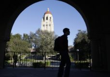 ILE - In this Feb. 15, 2012 file photo, a Stanford University student walks in front of Hoover Tower on the Stanford University campus in Palo Alto, Calif. Federal authorities have charged college coaches and others in a sweeping admissions bribery case in federal court. The racketeering conspiracy charges were unsealed Tuesday, March 12, 2019, against coaches at schools including Stanford, Wake Forest, Georgetown, the University of Southern California and the University of Southern California and University of California, Los Angeles. (AP Photo/Paul Sakuma, File)