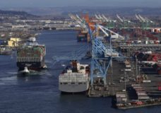 FILE- In this Tuesday, March 5, 2019, file photo the Cape Kortia container ship, left, heads into the Port of Tacoma in Commencement Bay in Tacoma, Wash. On Thursday, March 28, the Commerce Department issues the final estimate of how the U.S. economy performed in the October-December quarter. (AP Photo/Ted S. Warren, File)