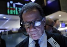 FILE- In this March 12, 2019, file photo a handheld device of trader Sal Suarino is reflected in his glasses as he works on the floor of the New York Stock Exchange. The U.S. stock market opens at 9:30 a.m. EDT on Thursday, March 21. (AP Photo/Richard Drew, File)