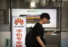 "A man looks at his smartphone as he walks past an electronics shop advertising phones from Huawei and Apple in Beijing, Friday, May 24, 2019. Stepping up a propaganda offensive against Washington, China's state media on Friday accused the U.S. of seeking to ""colonize global business"" by targeting telecom equipment giant Huawei and other Chinese companies. (AP Photo/Mark Schiefelbein)"