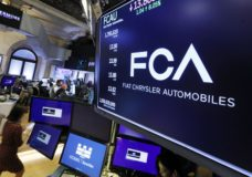 The Fiat Chrysler Automobiles logo appears above a post on the floor of the New York Stock Exchange, Tuesday, May 28, 2019. Fiat Chrysler is proposing a merger with French carmaker Renault aimed at saving billions of dollars for both companies. (AP Photo/Richard Drew)