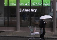 In this June 18, 2019, photo a man pulls a grocery cart as he walks in the rain past the stock ticker scroll board, showing a strong daily gain in the Dow Jones, outside Fidelity Investments in the Financial District of Boston. According to a survey by The Associated Press-NORC Center for Public Affairs Research, Americans are generally satisfied with their personal finances, but many lack confidence in their ability to afford retirement, an emergency expense or even their daily living costs (AP Photo/Charles Krupa)